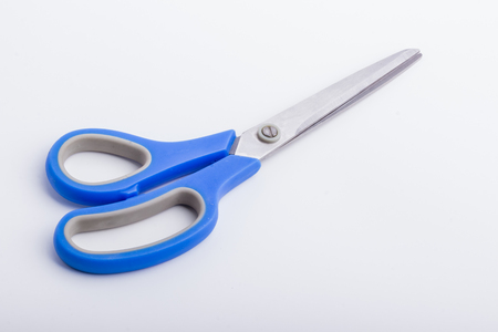 right handed: A closed pair of scissors with a blue grip, on a white surface. Stock Photo