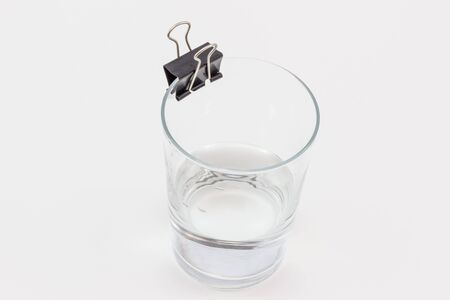 A glass with a little water in it and a binder clip on its rim, on a white surface. Stock Photo