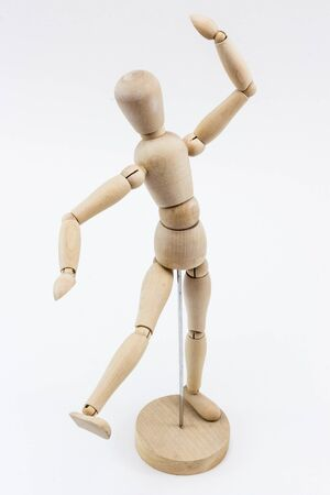 A wooden mannequin in a dance pose, on its stand, on a white surface. Stock Photo