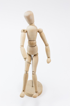 A wooden mannequin standing, on its stand, on a white surface.