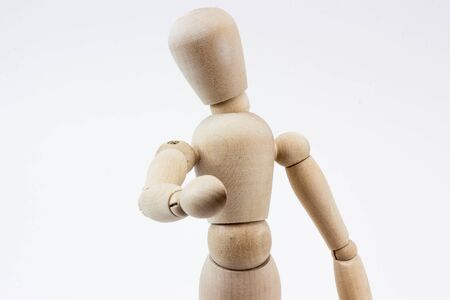 artificial model: The upper body of a wooden mannequin pointing at us, in front of a white background.