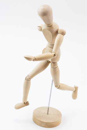 A wooden mannequin on its base, at a running position, looking down, on a white surface.