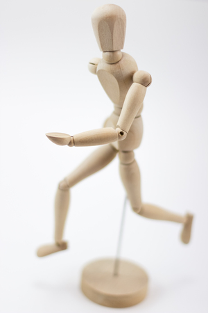 A wooden mannequin on its base, at a running position, looking at us, on a white surface.