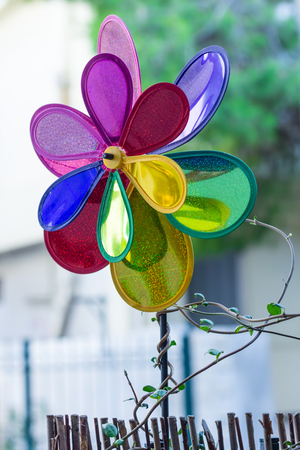 A double colorful wind mill, on a stick, with a climber plant on it.