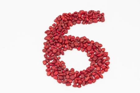 spot the difference: The number six made by little red stones, put one next to the other, on a white surface.