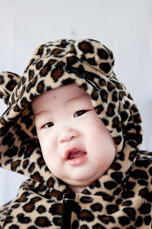 a beautiful smiling baby wrapped in a furry tiger skin