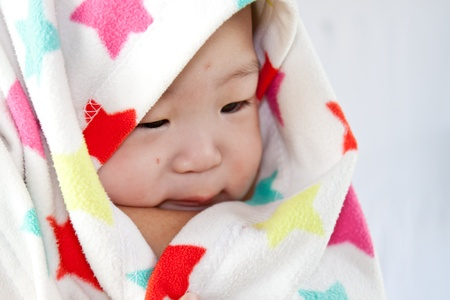 a beautiful smiling baby wrapped in a furry white blanket or towel