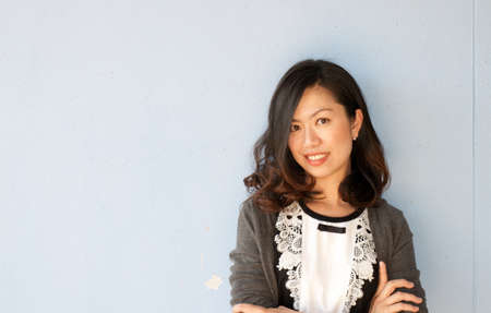 Beautiful Asian young businesswoman standing with hands folded against white background