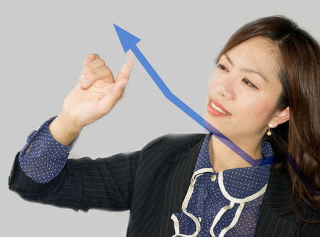 business woman drawing a graph on a glass window in an office - focus is on graph Stock Photo - 14330293