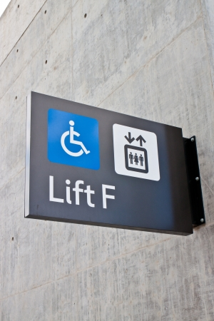 Handicapped wheelchair access logo sign on wall Stock Photo