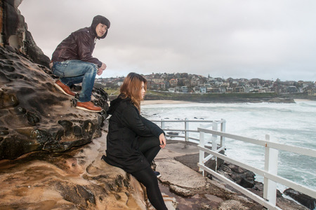 downunder: the couple walk pass the wall Stock Photo