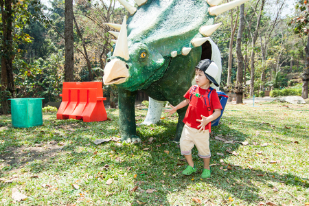 The boy is walking around dinosaur statue in Chiangmai Zoo, Chiangmai, Thailand