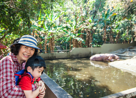 The boy is sitting around hippopotamus fence in Chiangmai Zoo, Chiangmai, Thailand