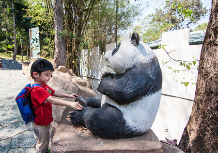 the boy is pitting around panda statue in Chiangmai Zoo, Chiangmai, Thailand