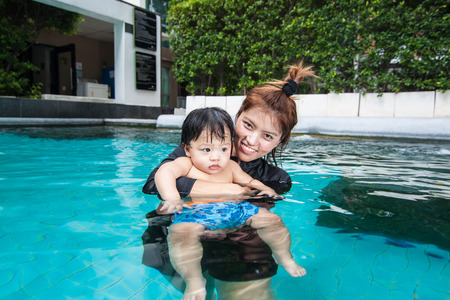The kid and mom play together in the pool, in the condominium Stock Photo