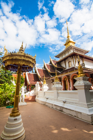 Ornate Buddhist temple complex featuring stone lions & a gilded chedi amid tropical greenery.