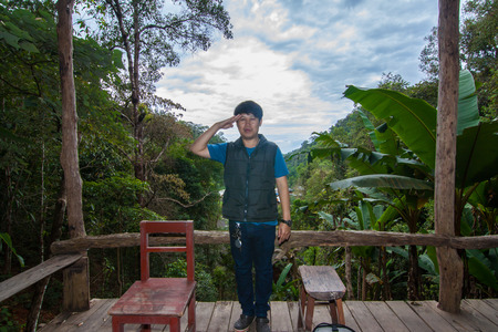 A man standing at the balcony in the forest 写真素材