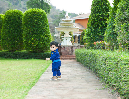 Thai boy in the pilot custome on the grass