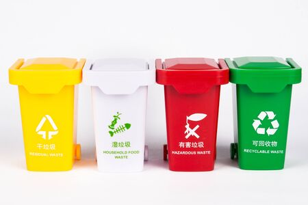 A row of colored trash cans on a white background, using a toy combination to express the concept of garbage sorting