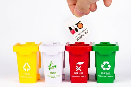 On a white background, there is a row of colored trash cans, one hand holding a card representing different kinds of garbage and throwing it into the trash can, using a toy combination to express the concept of garbage classification.