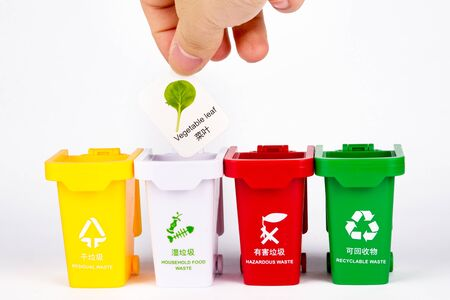 one hand holding a card representing different kinds of garbage and throwing it into the trash can, using a toy combination to express the concept of garbage classification.
