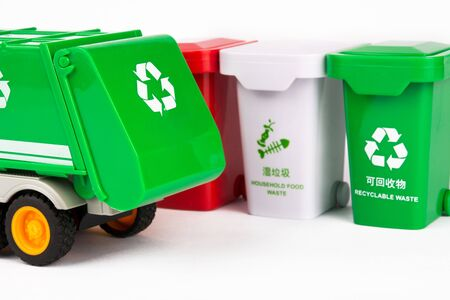 A row of colored trash cans and a garbage truck on a white background, using a toy combination to express the concept of garbage sorting