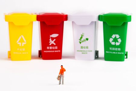 A villain model stands in front of a row of trash cans and is thinking about garbage sorting. Banco de Imagens