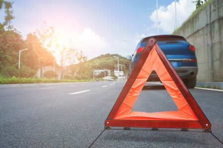 A broken car was parked in the far side of the road, and a triangular warning sign was placed behind the car.