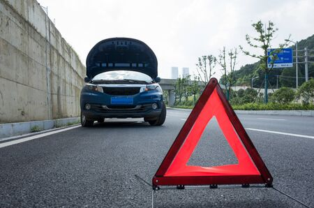 A broken car was parked in the far side of the road, and a triangular warning sign was placed in front of the car.