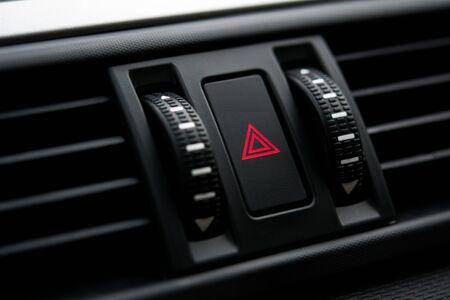 Closeup of hazard warning light switch on car control panel