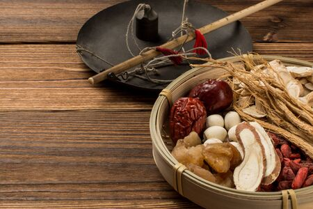 a plate of Chinese medicine and a medicinal scale on the board. Stockfoto