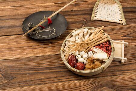 On the background of the wood grain, there is a rod and a plate of Chinese medicine. The plate contains ginseng, astragalus, licorice, medlar, red dates, longan and lotus seeds.