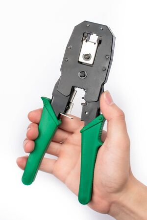 An Asian mans hand holding a wire cutter on a white background