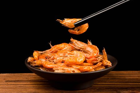 A bowl of dried river prawn on a wooden table with black chopsticks holding a river prawn