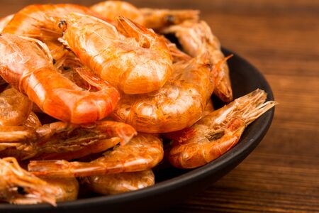 A plate of dried river prawns on a wooden table