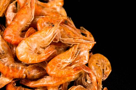 Dried river prawns close-up on a black background