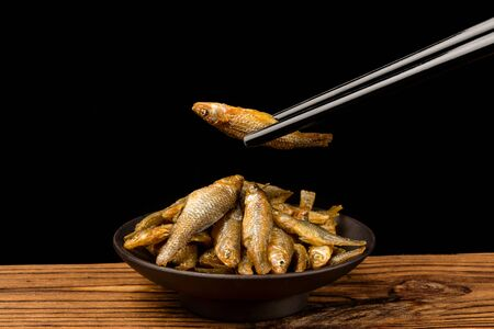 A bowl of dried fish on a wooden table with black chopsticks holding a dried fish Stok Fotoğraf