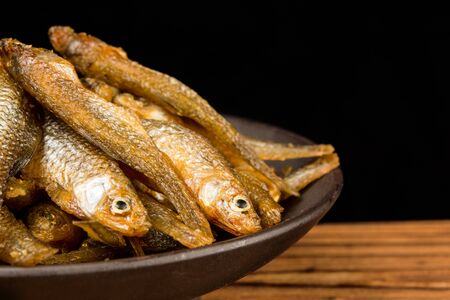 A bowl of small yellow dried fish on wooden table, close-up