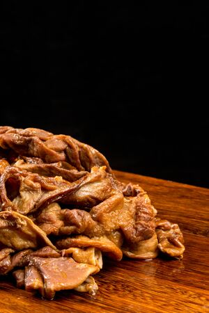 A bowl of preserved pig intestine on a wooden table