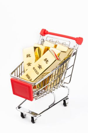 A shopping cart full of gold bars on white background Stock Photo