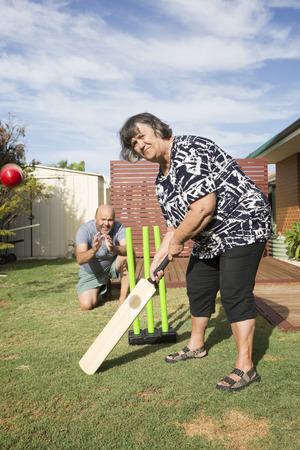 Grandmother having a turn at batting in Back Yard Cricket. Archivio Fotografico