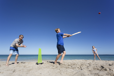 A family playing beach cricket in Australia.