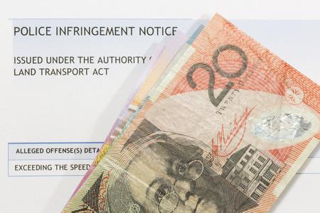 Australian currency on top of a speeding fine.
