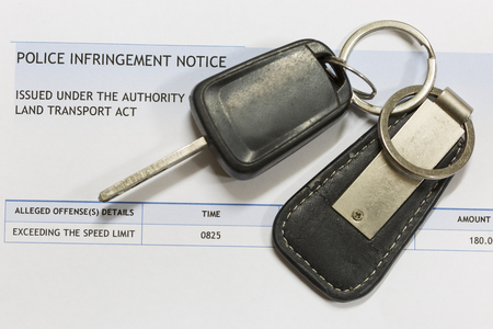 Car keys on top of a traffic infringement notice.