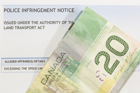Canadian paper currency on top of a police infringement notice.