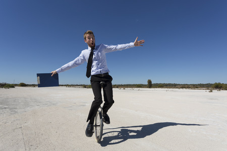 A businessman riding a unicycle, business concept.