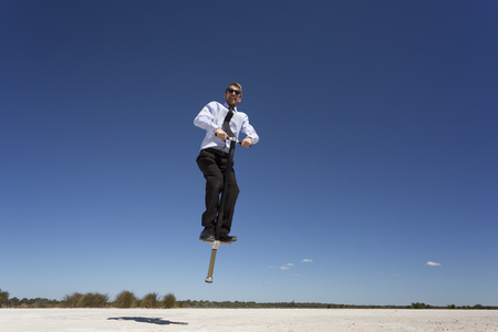A businessman jumping with a pogo stick.