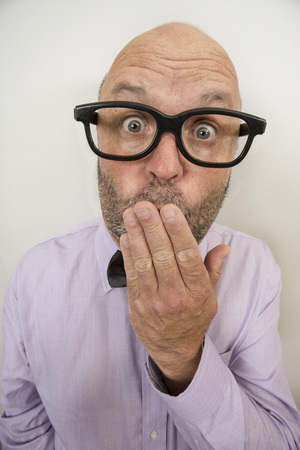 A man with his hand over his mouth, perhaps prudish or accidentally let out a secret. Stok Fotoğraf - 102810627