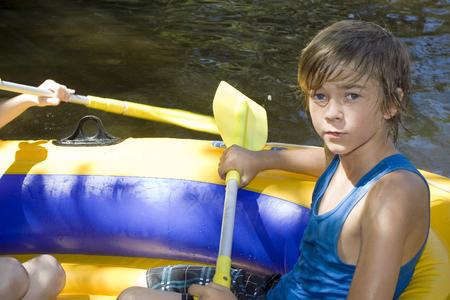 Retrato de un joven en un bote inflable, al aire libre.