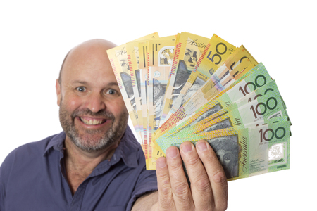 A guy fanning out a pile of Australian dollars to the camera with a happy expression. Stock Photo